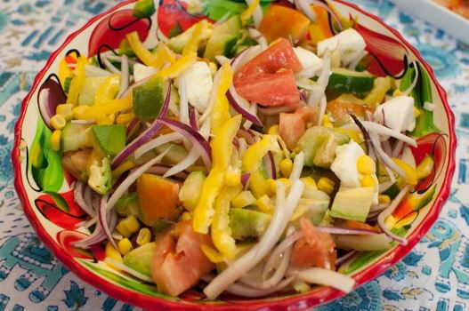 salad with corn, onion, tomato, mozzarella, peppers, cucumber and avocado